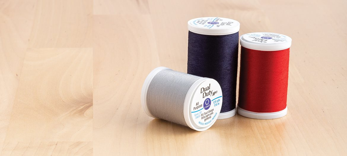 Coats Dual Duty XP Thread Black, Red and Grey Spools on Table for hand sewing or machine sewing